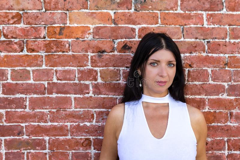 Stylish dark haired thoughtful woman. Posing in front of a red brick wall with copy space looking at camera royalty free stock photography