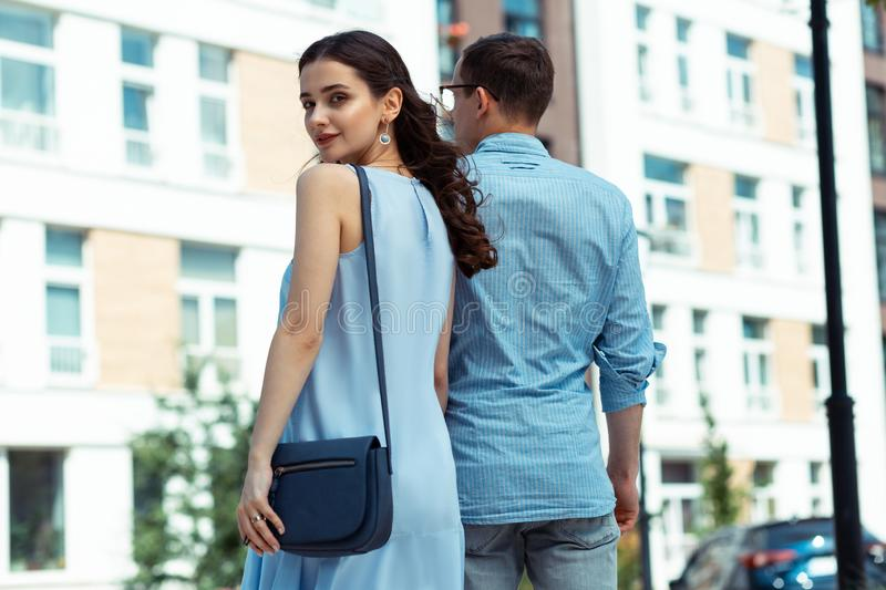 Stylish dark-haired wife walking hand in hand with husband stock photos