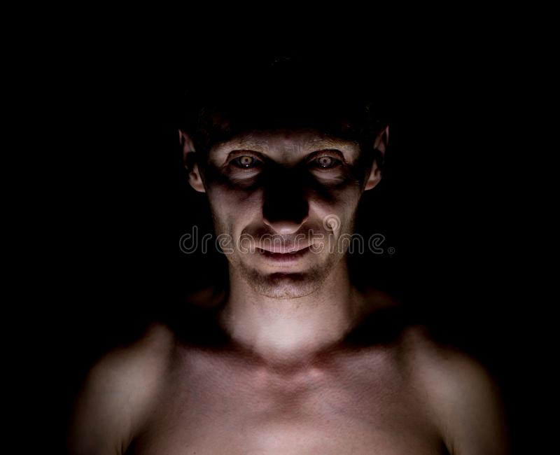 Stylish dark portrait of caucasian man who looks straight at you and looks like maniac. Expressive eyes stock photo
