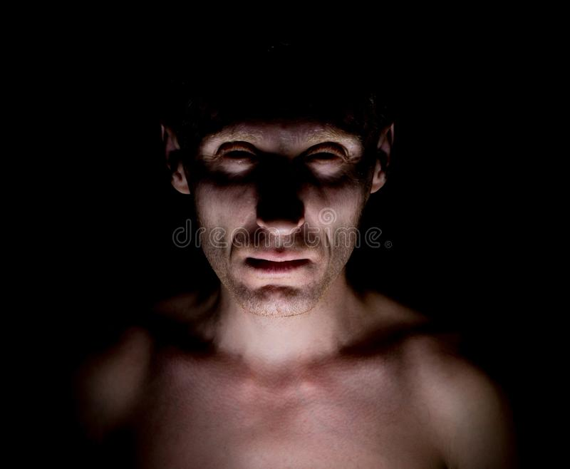 Stylish dark portrait of caucasian man who looks straight at you and looks like maniac. Expressive eyes stock photos