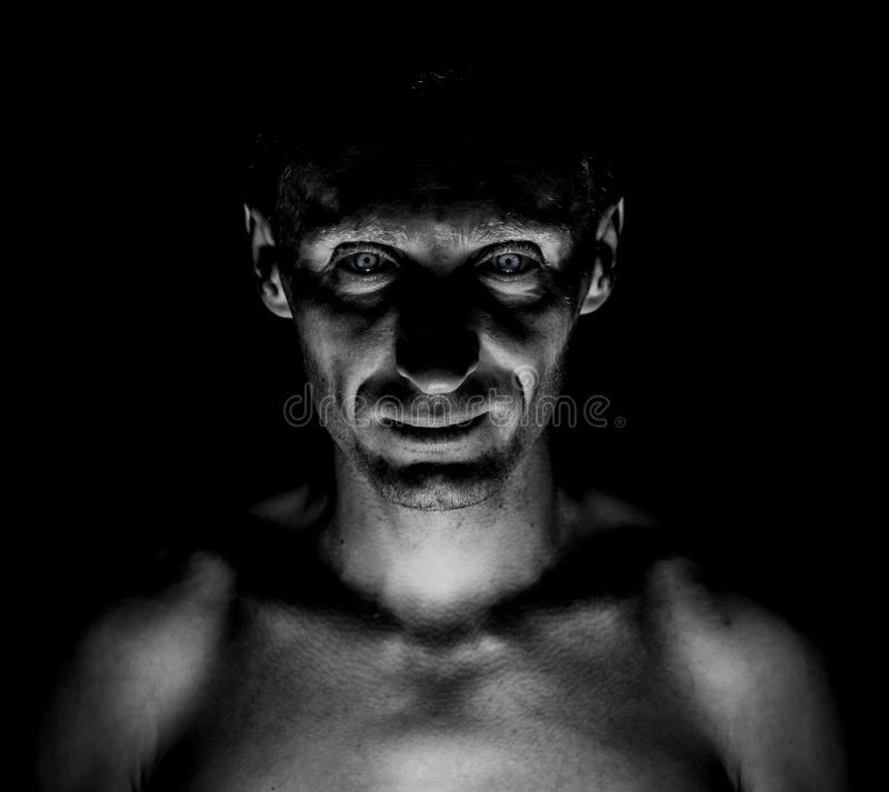 Stylish dark portrait of caucasian man who looks straight at you and looks like maniac. Expressive eyes. Black and white shot, low key lighting stock photography