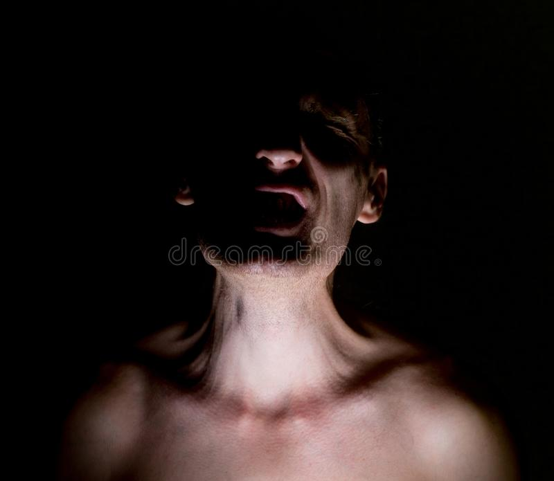 Stylish dark portrait of screaming adult caucasian man. Strong pain concept. On black royalty free stock photos