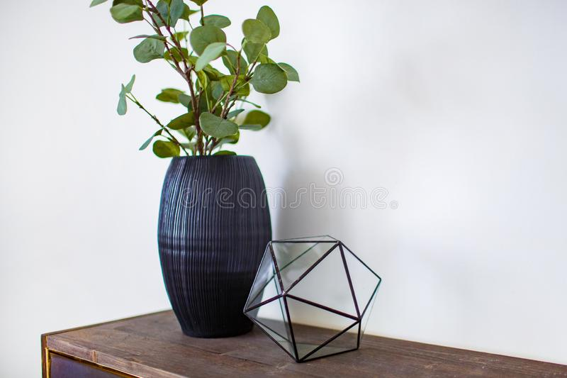 Stylish decor concept. Ceramic vase standing on wooden board close up stock images