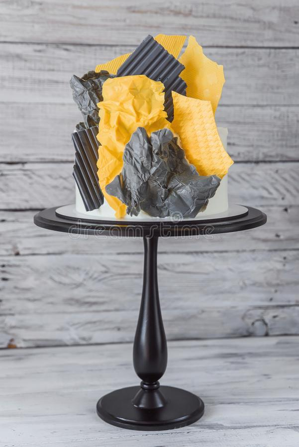 Stylish decorative cake of abstract shape in yellow and gray colors on the white wooden background. Gift for birthday royalty free stock image