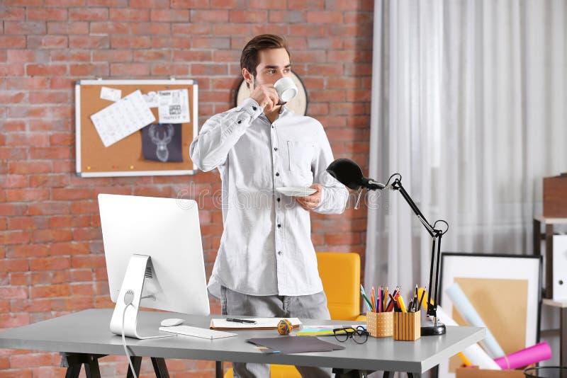 Stylish designer drinking coffee in office stock image