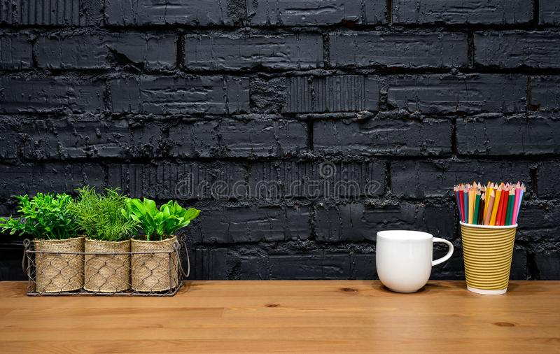 Stylish designer workspace mockup. Wooden desk with house plants, colorful pencils and white coffee mug on black brick wall background with copy space stock photography