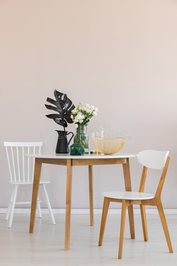 Stylish dining room with round table and elegant chairs, copy space on the empty wall stock photo