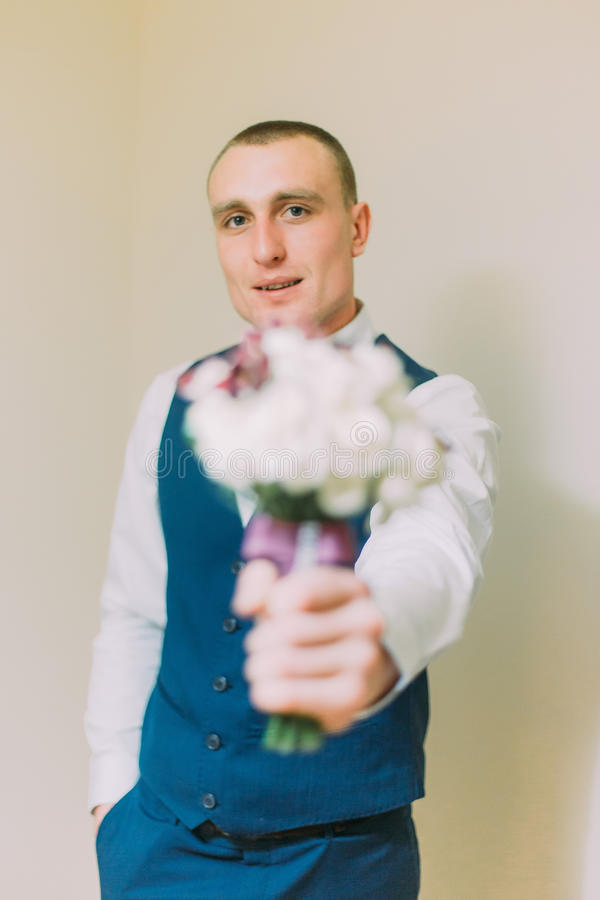 Stylish dressed man holding elegant bouquet of roses and proposing it to viewer.  stock photography