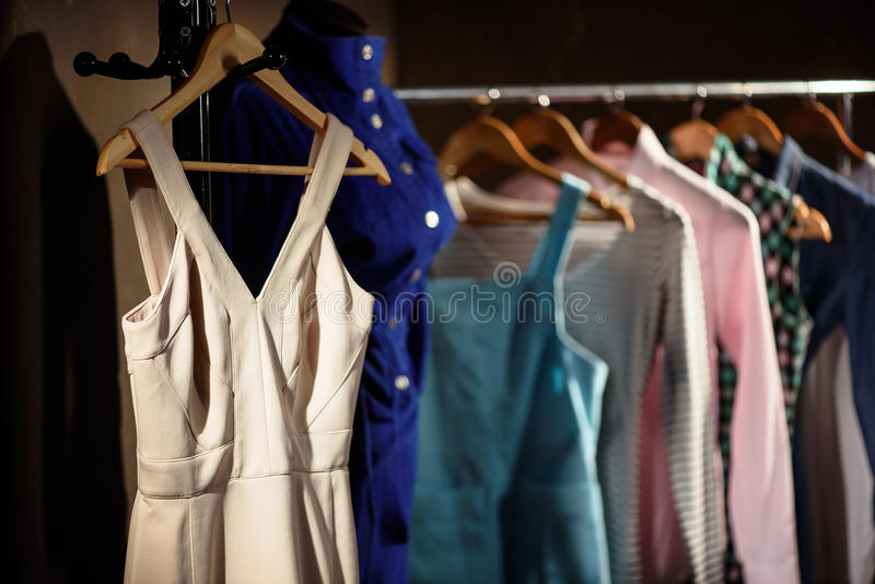Stylish dresses on stand in wardrobe royalty free stock photo