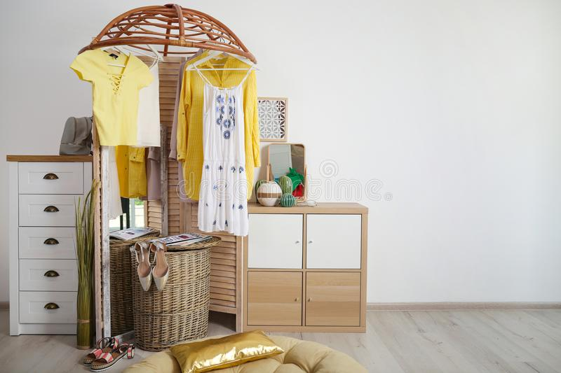 Stylish dressing room interior with wooden furniture. And clothes stock image