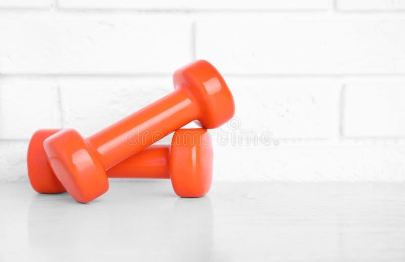 Stylish dumbbells on table against brick wall. Home fitness. Stylish dumbbells on table against brick wall, space for text. Home fitness stock photos