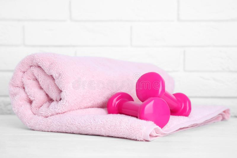 Stylish dumbbells and towel on table against brick wall. Home fitness. Stylish dumbbells and towel on table against brick wall, space for text. Home fitness royalty free stock photos