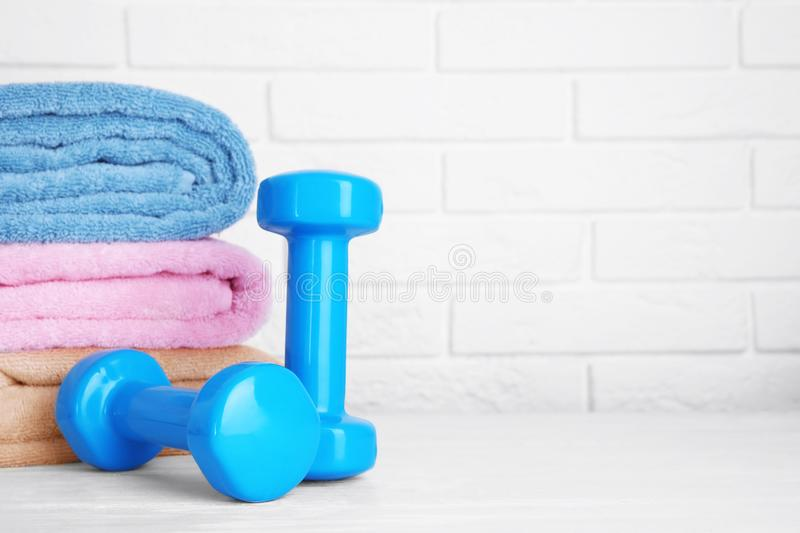 Stylish dumbbells and towels on table against brick wall. Home fitness. Stylish dumbbells and towels on table against brick wall, space for text. Home fitness stock photos