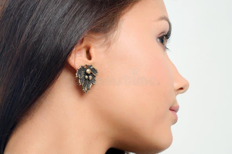 Stylish earring on beauty model ear. Close-up studio portrait of stock image