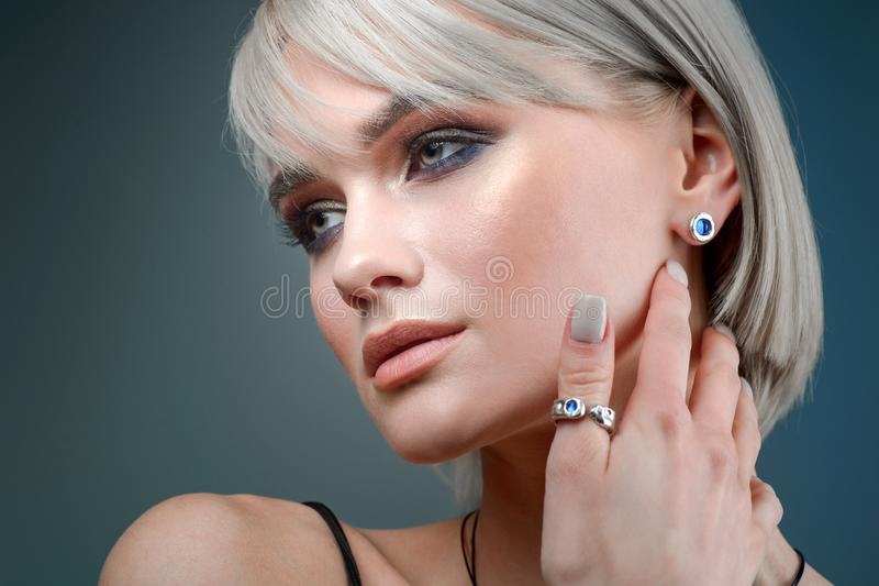 Stylish earring on the ear of the model. Macro studio portrait of a woman and decorations stock photos