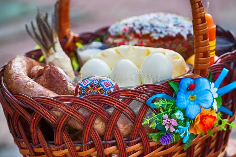 Stylish easter basket with food. horseradish, butter, sausage and painted eggs in wicker basket. Happy easter stock image