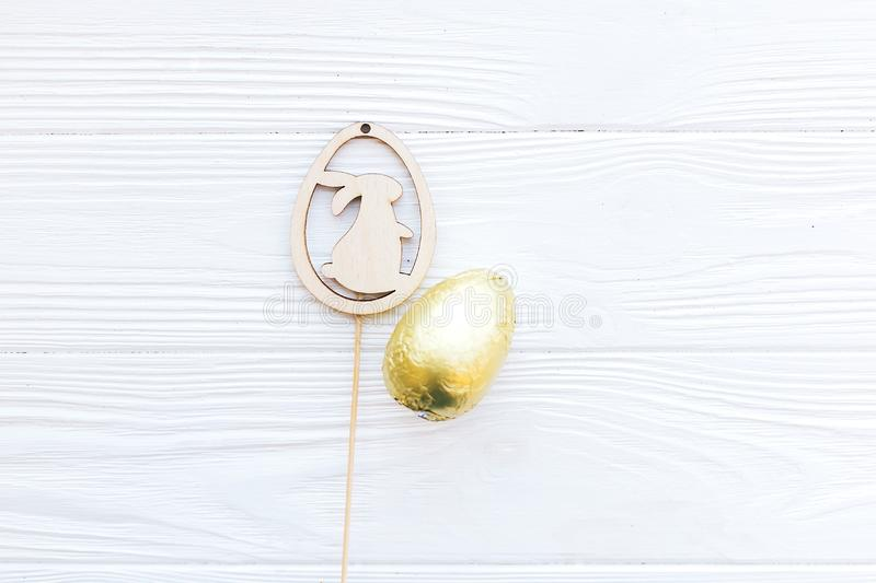 Stylish Easter chocolate egg in golden foil and simple wooden bunny  decoration on white wooden background, flat lay with space. For text. Happy Easter. Holiday stock photo