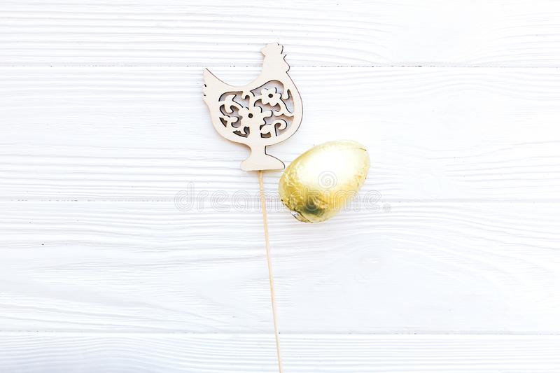 Stylish Easter chocolate egg in golden foil and simple wooden chicken decoration on white wooden background, flat lay with space. For text. Happy Easter royalty free stock photos