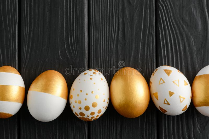 Stylish Easter decoration set. On black wooden background. Eggs painted with golden patterns. Happy Easter design stock photos
