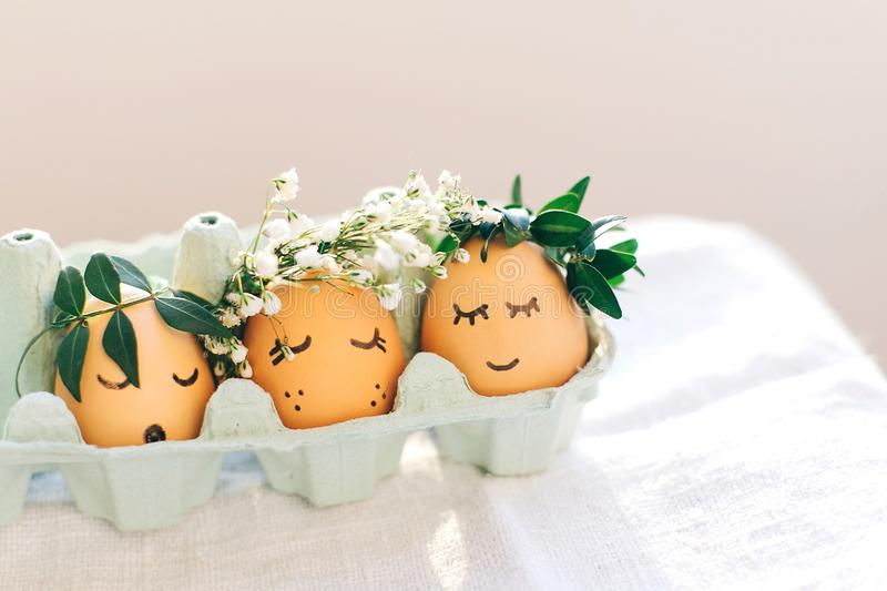 Stylish Easter eggs with cute faces in floral wreath crowns in carton tray on rustic background. Modern easter eggs with flowers stock image