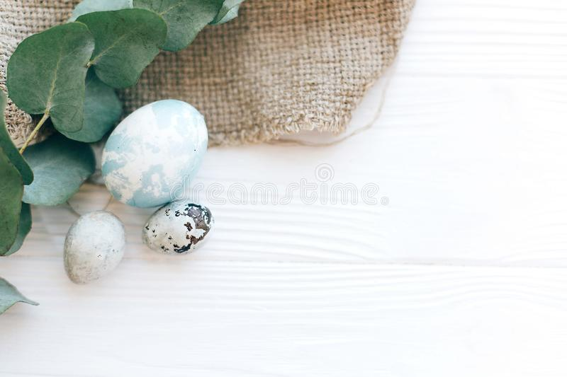 Stylish Easter eggs on rustic fabric with eucalyptus branch on white wooden background. Modern pastel eggs painted with natural royalty free stock images
