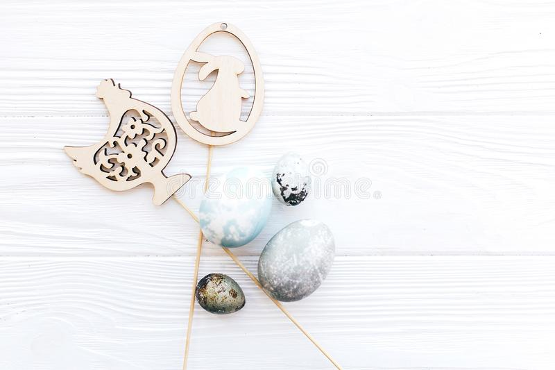 Stylish Easter eggs and simple wooden bunny and chicken decorations on white wooden background, flat lay with space for text. stock photo