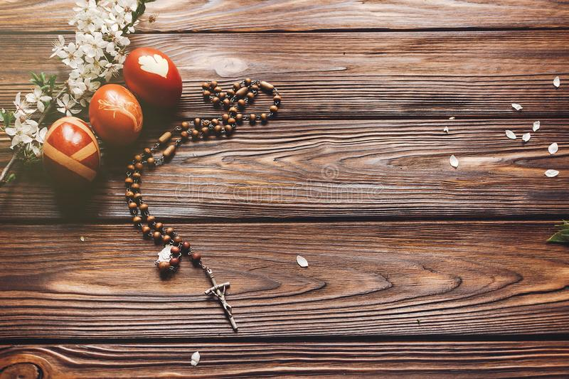 Stylish easter eggs and wooden rosary with cross and cherry fl royalty free stock photo