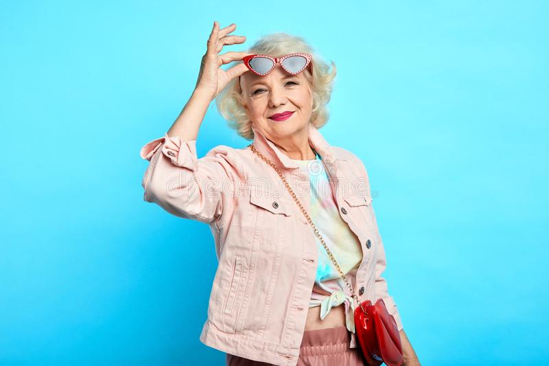 Stylish elderly woman in sunglasses and trendy clothes is smiling. And looking at the camera. happiness, beuty, free time, spare time royalty free stock photography