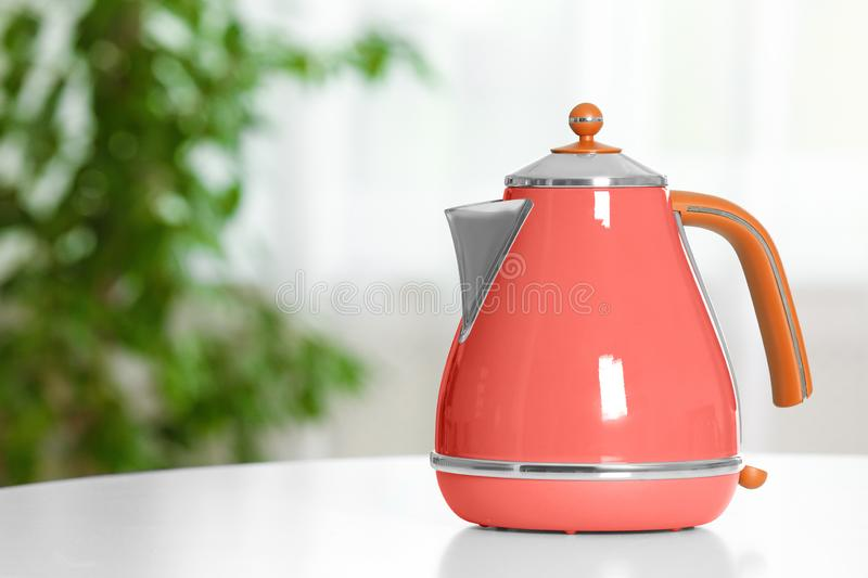 Stylish electrical kettle on table against blurred room interior. stock photography