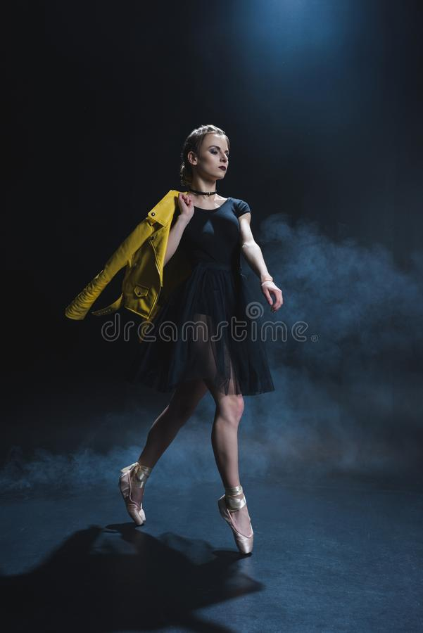 Stylish elegant ballerina in pointe shoes and black tutu and yellow leather jacket in studio. With smoke stock photos