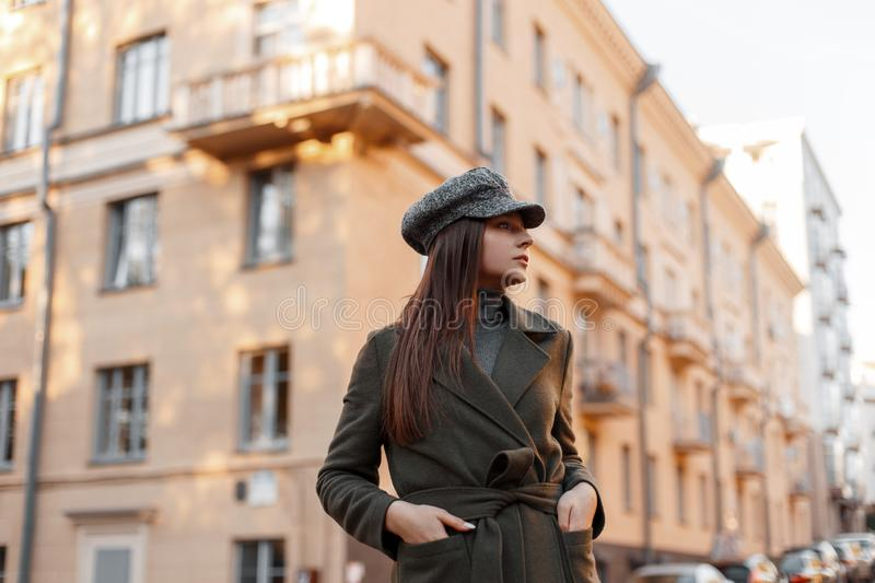 Stylish elegant beautiful young girl in a vintage hat and green fashion coat walking on a European street near the building. stock image