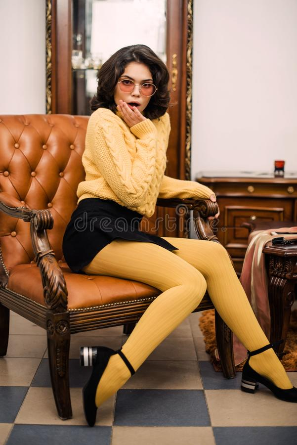 Stylish elegant brunette woman in beauty rich interior, wearing black dress royalty free stock image