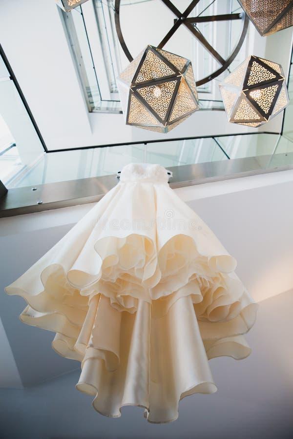 Stylish elegant wedding dress hanging in the room royalty free stock image