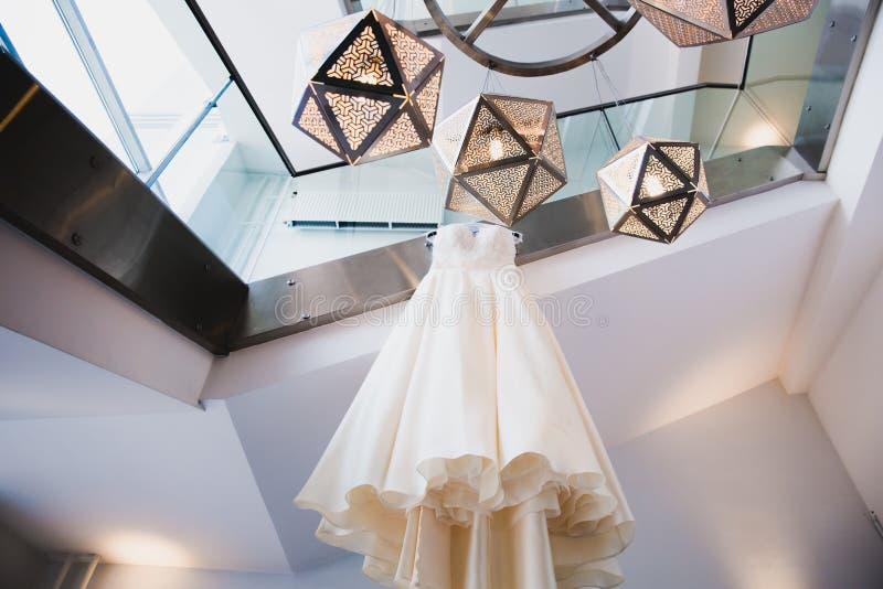 Stylish elegant wedding dress hanging in the room stock photography