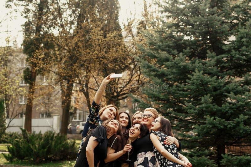Stylish elegant women taking funny selfie at celebration sunny in park, luxury happy life concept royalty free stock image