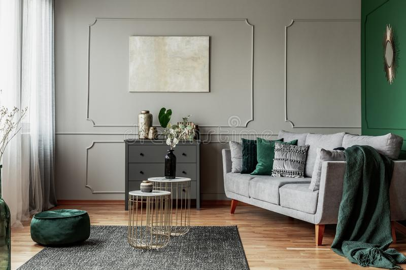 Stylish emerald green and grey living room interior design with abstract painting on the wall. Stylish emerald green and grey living room interior design with royalty free stock image