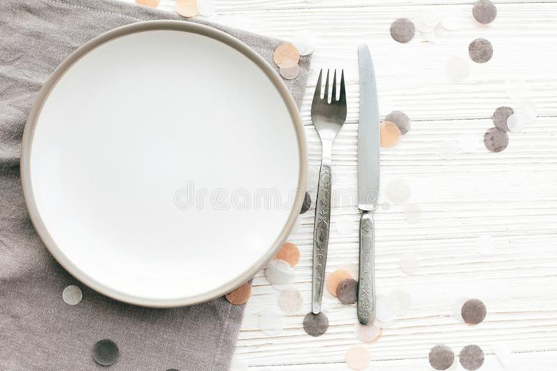 Stylish empty plate with vintage fork and knife on napkin on white table with confetti, flat lay. Modern set, serving for. Reception and celebration. Party and royalty free stock photo