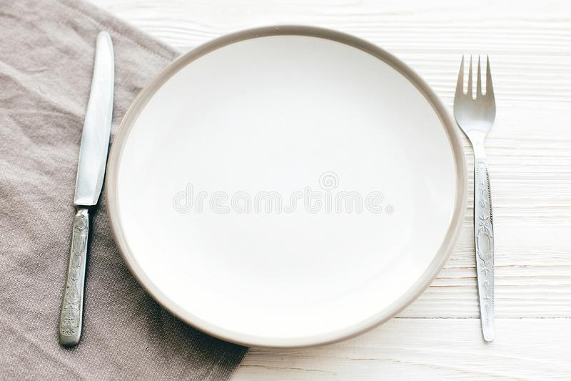 Stylish empty plate with vintage fork and knife on napkin on white table, top view. Modern set, serving for reception and. Celebration. Party and diet concept royalty free stock photography