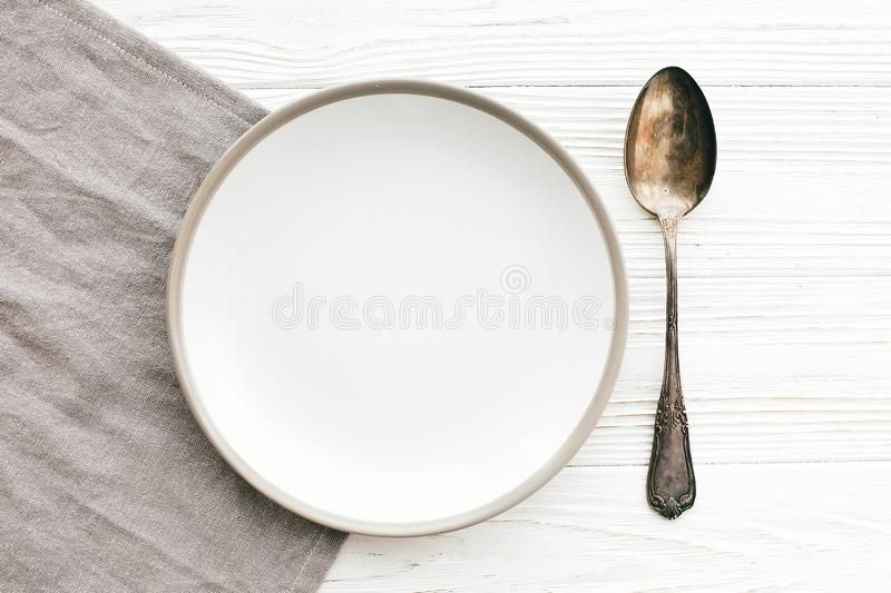 Stylish empty plate with vintage spoon on napkin on white table, flat lay. Modern set, serving for reception and celebration. Party and diet concept. Copy royalty free stock photo