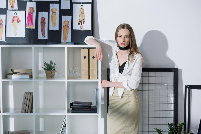 Stylish fashion designer leaning on bookshelves. At office stock photo