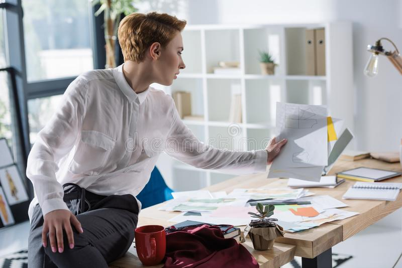 Stylish fashion designer with lot of paperwork sittin. On work desk stock image