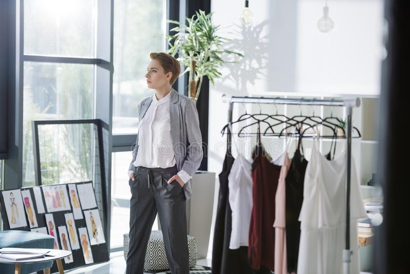 Stylish fashion designer at modern office with lot of dresses. On hangers stock image