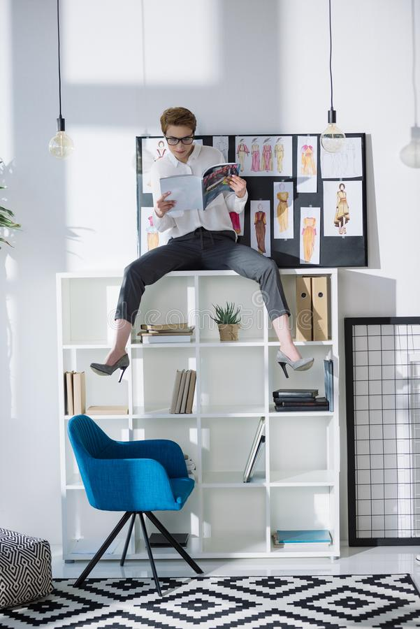 Stylish fashion designer sitting on bookshelves. And reading magazine royalty free stock photos