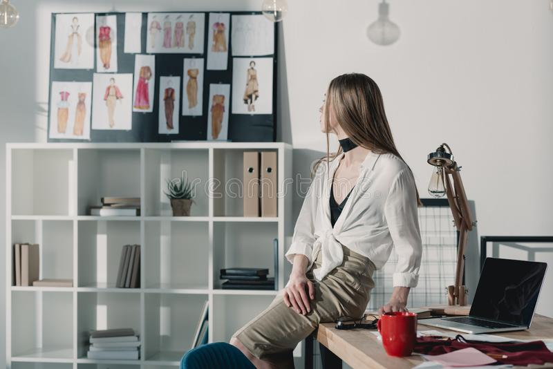 Stylish fashion designer sitting on table at office and looking. At sketches royalty free stock image