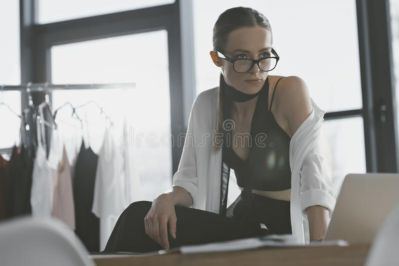 Stylish fashion designer sitting on work desk. At office royalty free stock photography