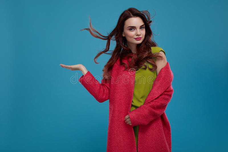 Stylish Fashion Model Girl Presenting Point On Blue Background. Happy Fashion Model Girl In Stylish Clothes Presenting Point On Blue Background, Proposing royalty free stock images