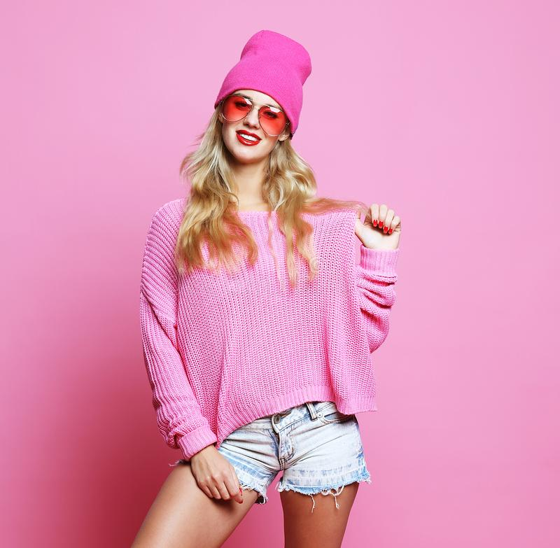 Stylish fashion portrait of trendy casual young woman in pink pulover and hat, posing over pink background. Hipster style stock photography