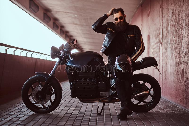 Stylish fashionable biker dressed in a black leather jacket with sunglasses fix the hair and holds helmet while sitting royalty free stock images
