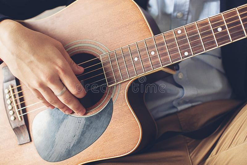 Stylish, fashionable man in a blue shirt, dark blue jacket and brown pants playing guitar. The concepts of hobby, passion and stock photos