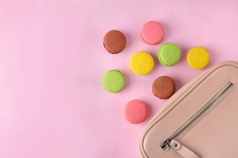 Stylish fashionable pink bag and French macaroon cakes on a bright trendy pink background. female accessory concept. top view stock image